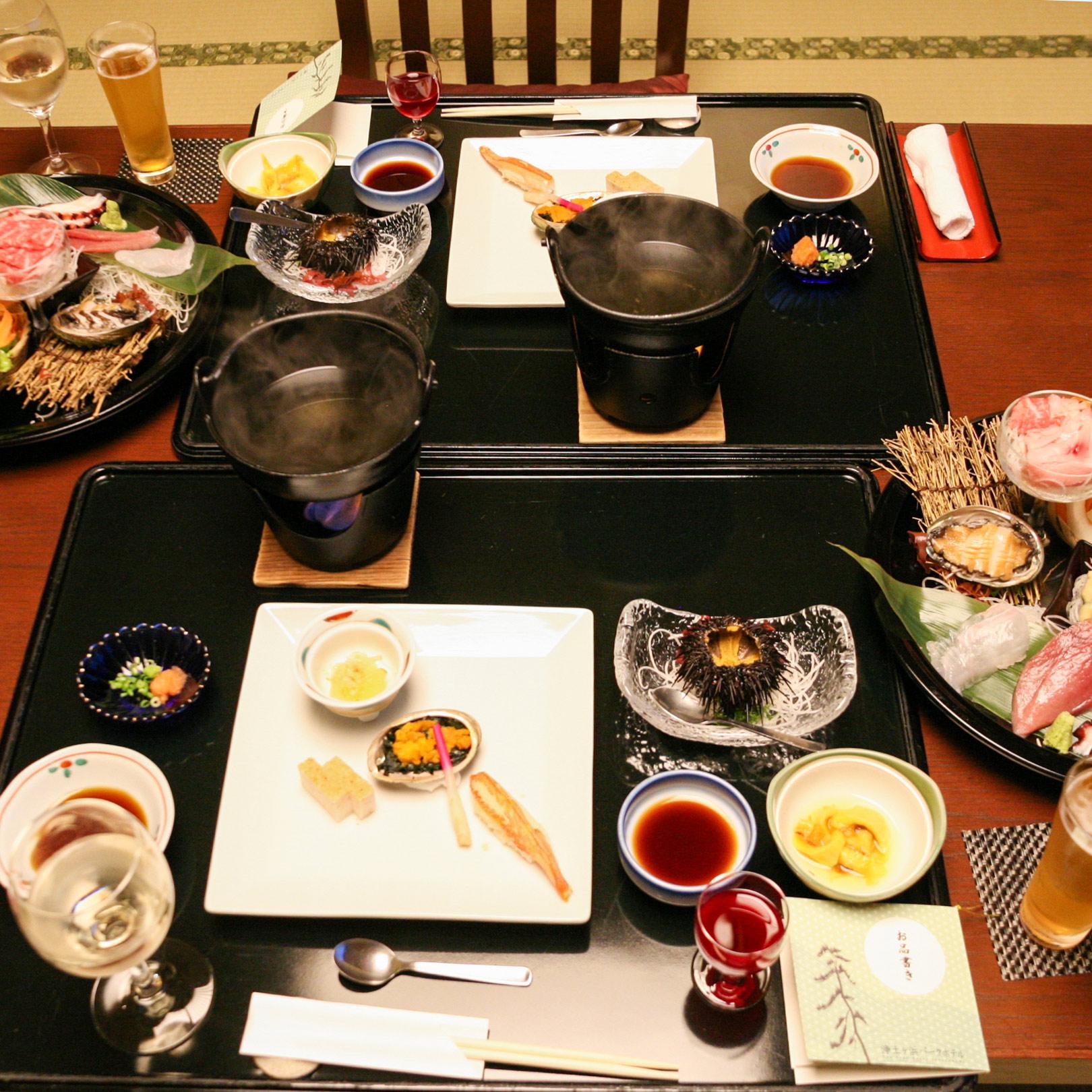 客室は旅館対応なので、希望すれば客室で夕食のサービスを受けられる。地元産の食材を使用した料理でテーブルがいっぱいになる。
