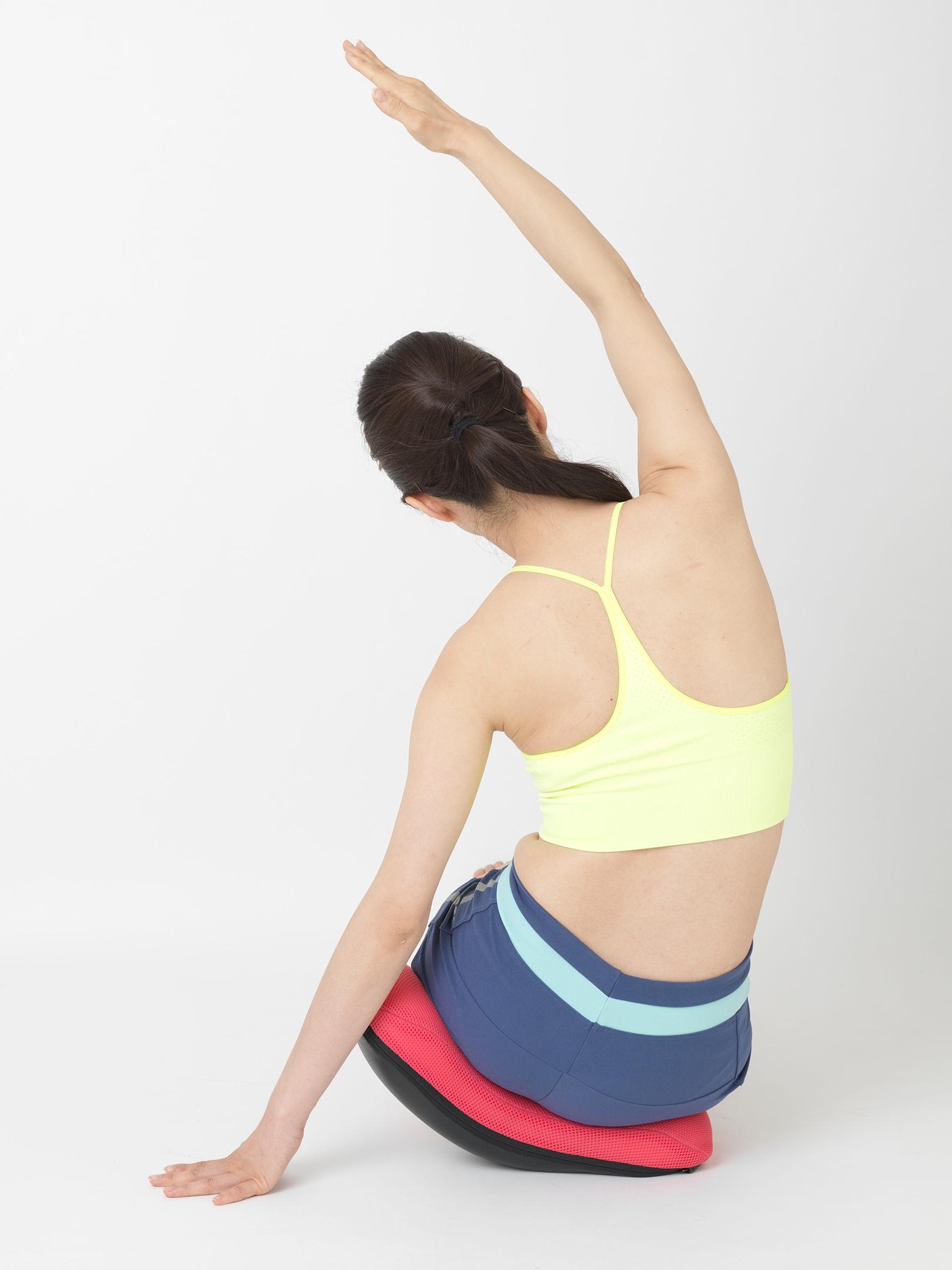 クッションの凹んだ部分にお尻を乗せて腕を上げ、息を吐きながら体を傾ける「ウエストストレッチ」。腕を伸ばした方のお尻を下げることでウエストがより伸びやすくなる。
