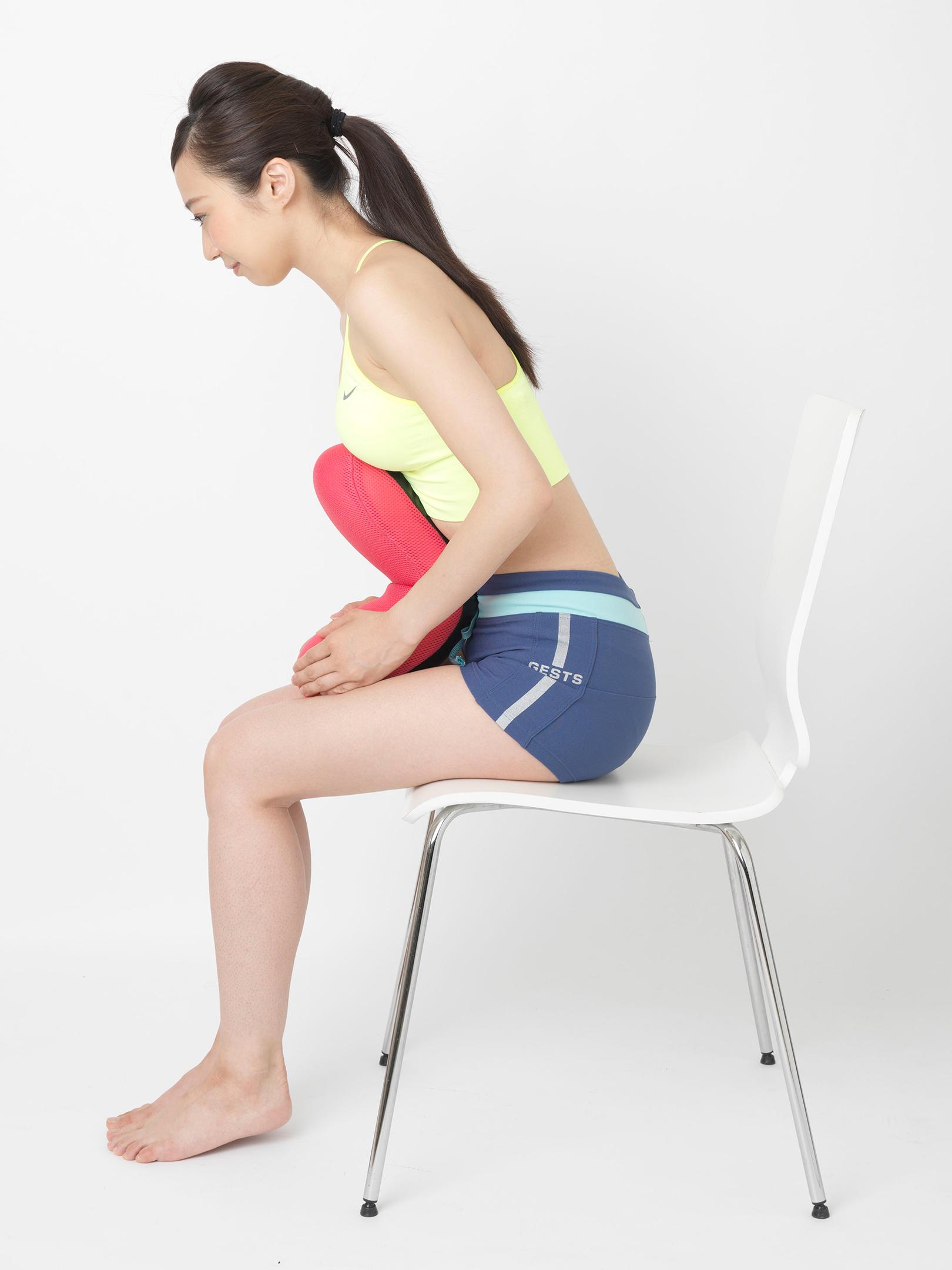 こちらは、太ももの上にクッションを置き、両手で持って胸でクッションを折り曲げるようにする「お腹」エクササイズ。クッションを曲げるのに、かなりの負荷を必要とする。
