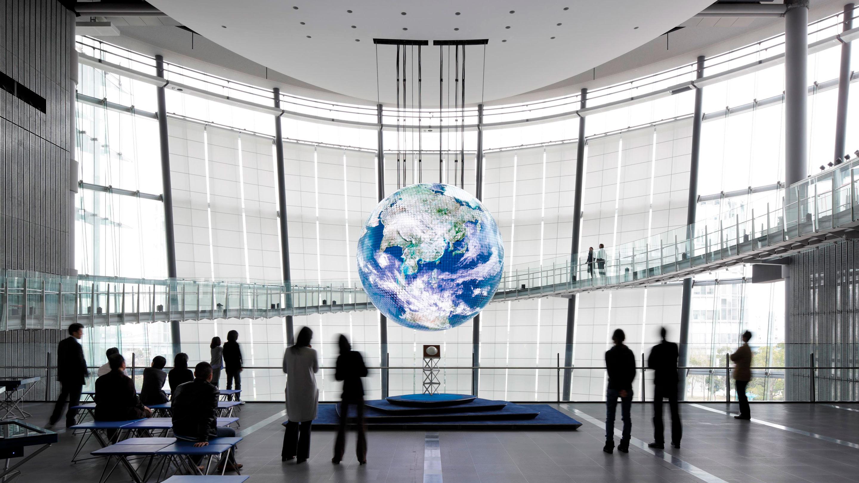 日本科学未来館を象徴する巨大な地球ディスプレイ「Geo-Cosmos(ジオ・コスモス)」。1階から6階までの壮大な吹き抜け空間で、地球の様子をほぼリアルタイムで映し出す。1,000万画素を超える高解像度の有機ELパネルを使った世界初の地球ディスプレイ。「宇宙から見た輝く地球の姿を多くの人と共有したい」という毛利 衛館長の思いから生まれた。
