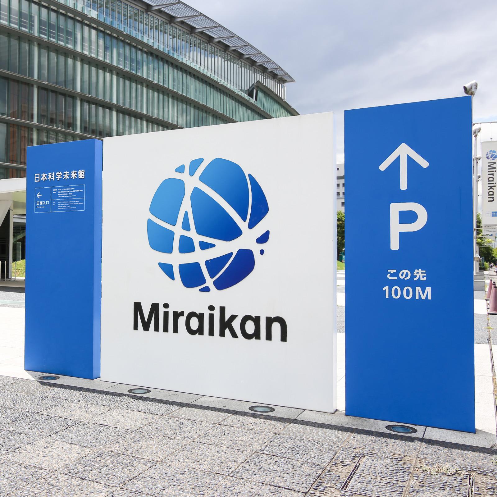 Miraikanの愛称と青いシンボルマーク。地球と衛星軌道、細胞分裂、人と人、人と情報といった地球上のさまざまなネットワーク、電子の動きなどをイメージさせる。
